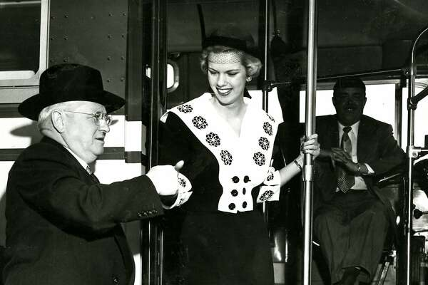 1950's: Mayor Elmer Robinson assists Jane St. Clair, Miss Modern Transporation, off a new San Francisco Muni bus. June 14. 1950