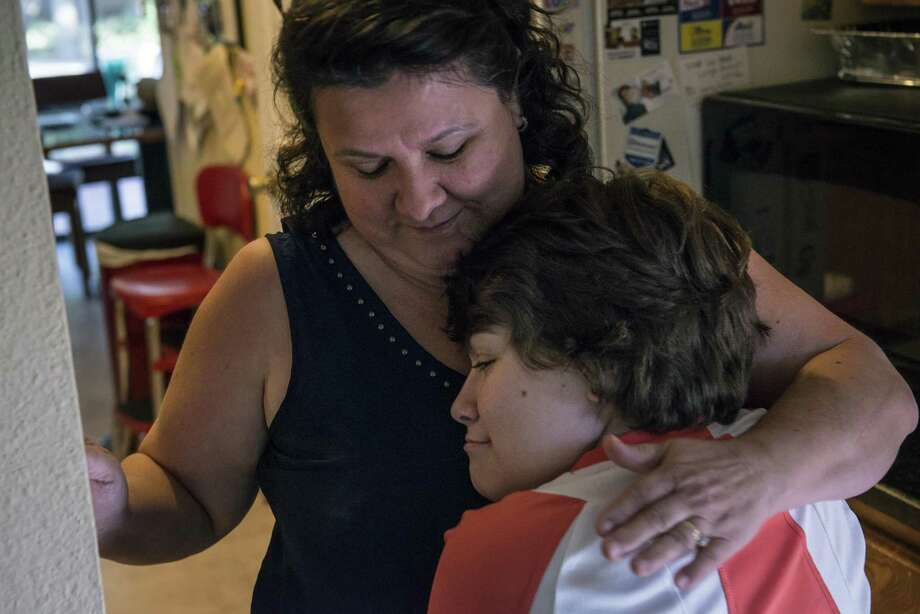 Cynthia Oyler, 17, who suffers from Spina Bifida, hugs her mother Nora Oyler in their family's home on Aug. 10, 2015. Oyler benefited from the early childhood intervention program, which gave her access to physical therapy and other treatments after being born with the debilitating condition of Spina Bifida. The GOP health care plan jeopardizes such treatments even further. Photo: Matthew Busch /For The Express-News / © Matthew Busch