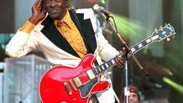 Rock 'n' roll legend Chuck Berry listens for the crowd to sing to him during a performance of his hit song 'Johnny B. Goode,' at the Concert for the Hall of Fame in Cleveland, in this Sept. 2, 1995, file photo. Berry died Saturday.