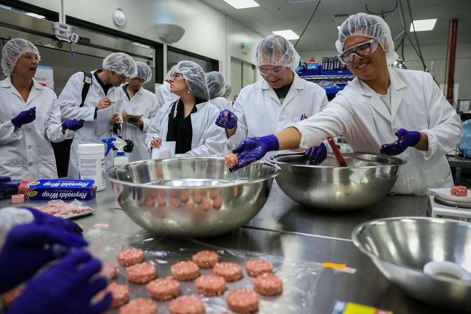 "Kevin Hong (right) throws a ball of plant-based ""meat"" into a bowl while preparing food in the test kitchen at the Impossible Foods headquarters in Redwood City. Photo: Gabrielle Lurie, The Chronicle"
