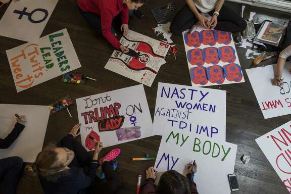 A poster drawing party is held Jan. 17 in preparation for the Women's March. Customers flocked to buy poster board and other materials for signs ahead of women's marches, a consumer research company says.