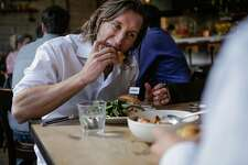 Customer Jay Gierak takes a bite out of an Impossible burger during lunch at Cockscomb restaurant in San Francisco, California, on Wednesday, March 22, 2017.