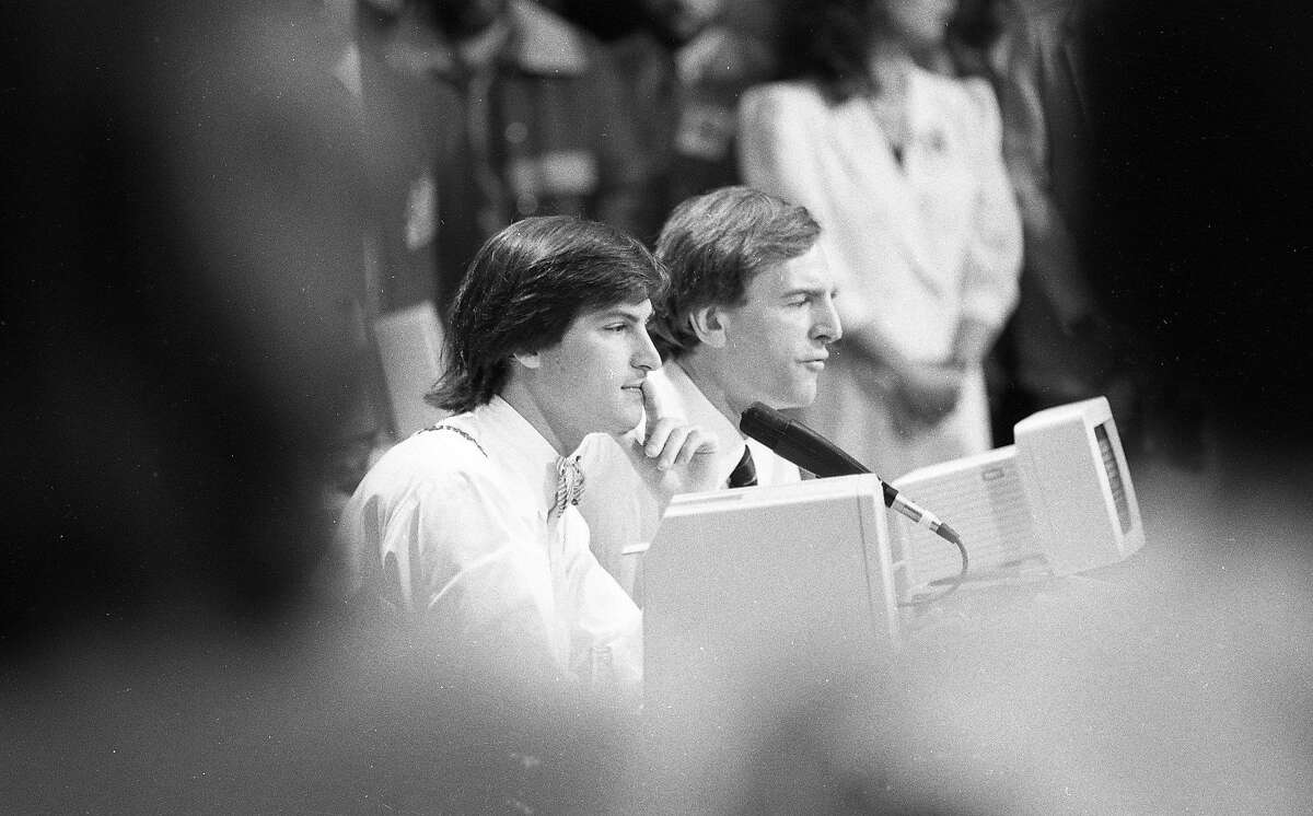 """Apple executives John Sculley and Steve Jobs speak with the press at the """"Apple II Forever"""" event at Moscone Center in San Francisco on April 23, 1984."""