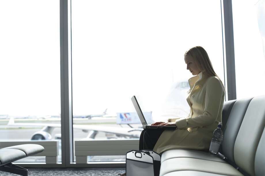 A woman looks at her laptop at an airport.