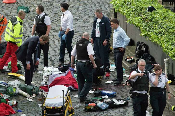 """MP Tobias Ellwood, left, stands amongst emergency services outside the Palace of Westminster, London, Wednesday.  Police say they are treating the attack """"as a terrorist incident until we know otherwise."""""""