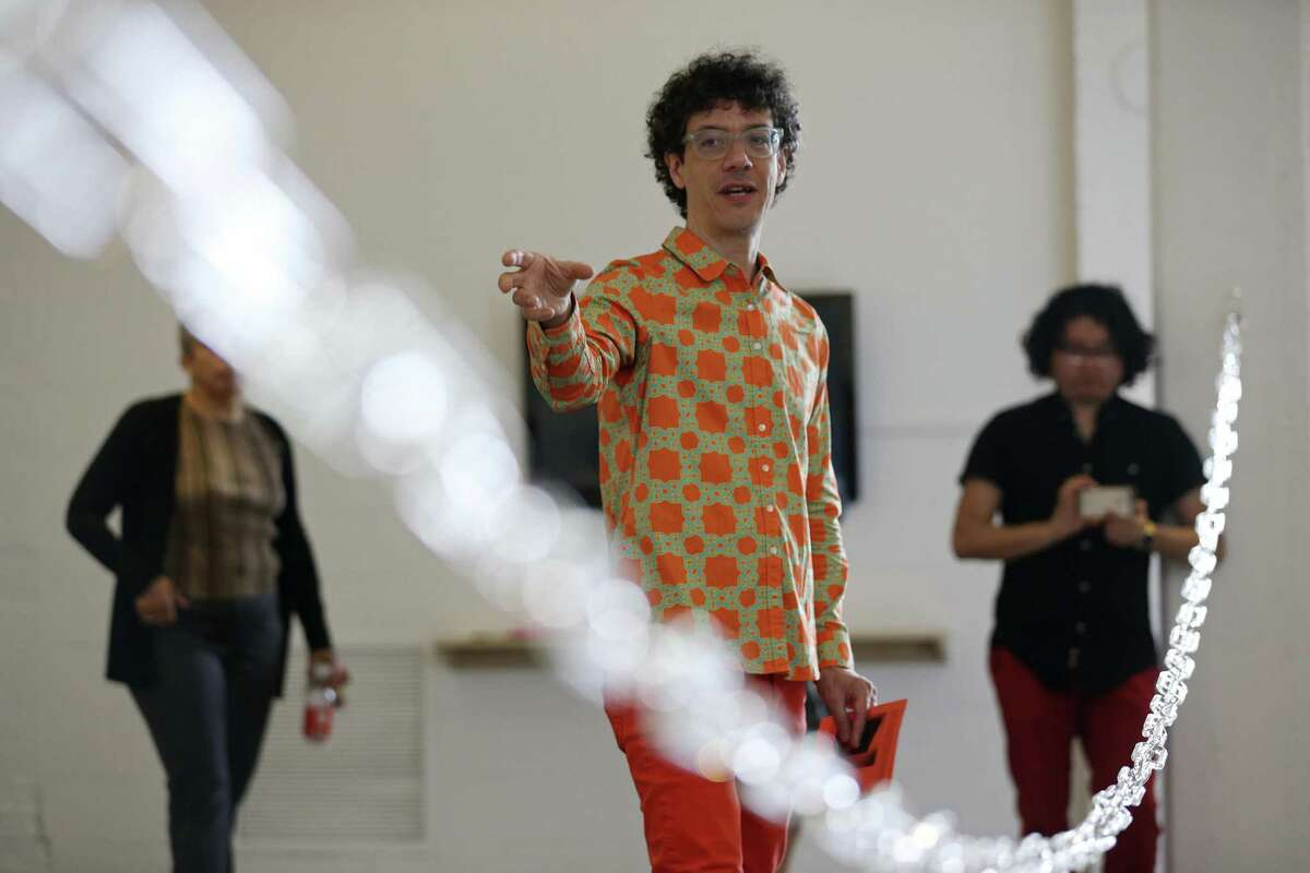 Nicholas Frank of Milwaukee, Wisconsin, stands behind a 32-foot chain made out of glass that is part of his exhibition at Artpace.