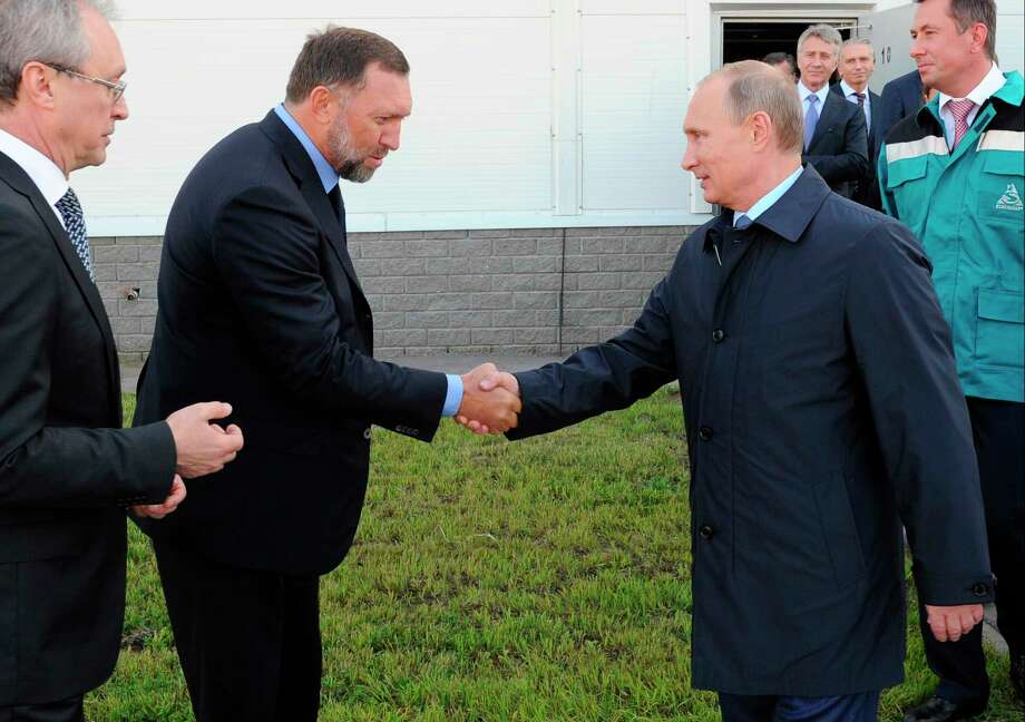 Russian President Vladimir Putin, right, shakes hands with metals magnate Oleg Deripaska in Kstovo, in September 2014. President Donald Trump's former campaign chairman, Paul Manafort, secretly worked for Deripaska to advance the interests of Putin a decade ago. Photo: Mikhail Klimentyev, POOL / RIA Novosti Kremlin