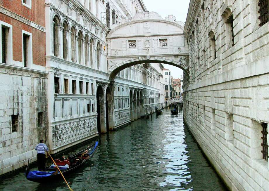 This Nov. 9, 2013, photo shows the Bridge of Sighs in Venice. The bridge's name was bestowed by the poet Lord Byron, describing the sighs of condemned prisoners taking a final view of Venice as they walked to their cells. You have to pay to walk inside the covered bridge, but can get a good, free, view of the outside from the Paglia Bridge, known as Ponte della Paglia. (AP Photo/Michelle Locke) ORG XMIT: NYET455 Photo: Michelle Locke / AP