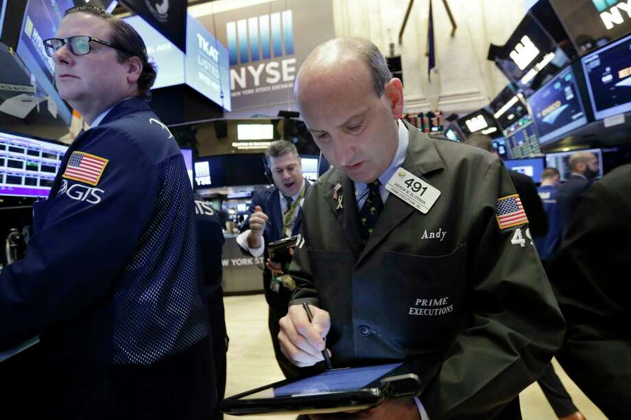 Trader Andrew Silverman, right, works on the floor of the New York Stock Exchange, Wednesday, March 22, 2017. Stocks are treading water in early trading as gains in high-dividend stocks are outweighed by drops in banks and other sectors. (AP Photo/Richard Drew) Photo: Richard Drew, STF / AP