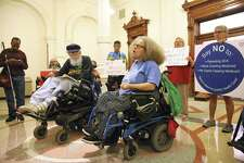 Stephanie Thomas comes forward to speak her mind as disabled citizens and supporters assemble in front of Gov. Abbott's office in the State Capitol to urge the governor to use his influence to get the Congress to reject the American Health Care Act  on March 22, 2017.  Bob Kafka (left center) an organizer for listens with about 15 other demonstrators Wednesday afternoon.