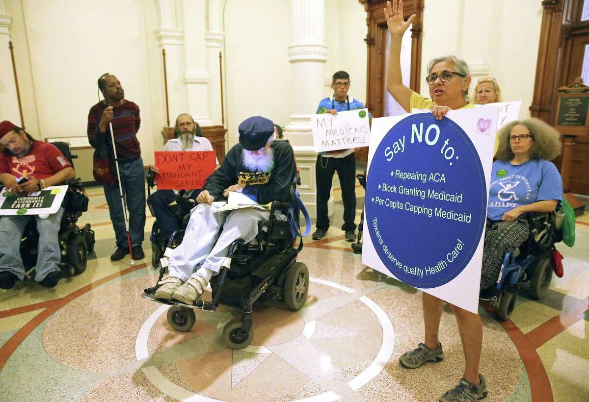 Cathy Cranston an attendent who works in the Austin community, steps forward with a sign expressing her sentiment as disabled citizens and supporters assemble in front of Gov. Abbott's office in the State Capitol to urge the governor to use his influence to get the Congress to reject the American Health Care Act on March 22, 2017.