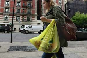 A woman carries groceries in plastic bags. A bill before the Texas Senate would keep cities from banning plastic bags like governments have done in Austin, Laredo, Brownsville and South Padre Island.