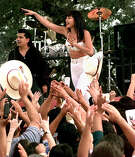 """Both the Tejano star Selena and Jennifer Lopez in """"Selena,"""" above, proved that Latinas could be crossover stars and draw audiences. But Hollywood still hasn't learned that lesson. iplaying Selena holds the microphone out towards the crowd which is made up of area residents during the filming of the Monterray concert scene today in Poteet. Backup singer Pete Astudillo, left plays himself in the movie. FOR METRO THELMA 10-19-96"""