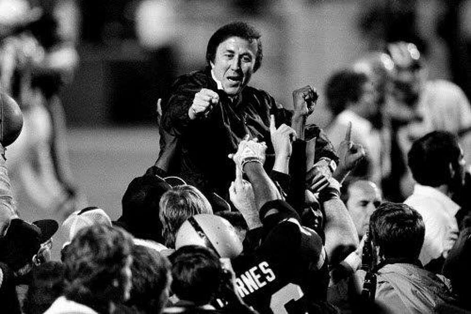 Victorious coach Tom Flores gestures to members of the Los Angeles Raiders as they carry him off the field after their 38-9 victory over the Washington Redskins in Super Bowl XVIII in Tampa Jan. 23, 1984. The Oakland Raiders will face the Tampa Bay Buccaneers in Super Bowl XXXVII in San Diego Sunday, Jan. 26, 2003. (AP Photo/files) Photo: AP