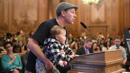 Teacher Leon Sultan holds his son Teddy Sultan, 2, while advocating for affordable teacher housing during a Board of Supervisors hearing on Wednesday, March 22, 2017, in San Francisco.