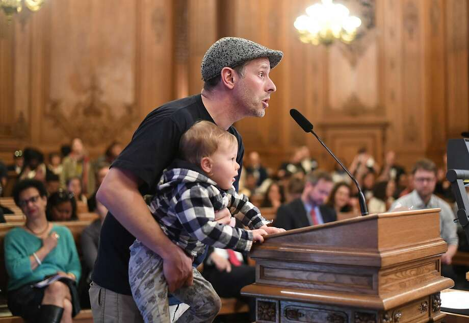 Teacher Leon Sultan holds his son Teddy Sultan, 2, while advocating for affordable teacher housing during a Board of Supervisors hearing on Wednesday, March 22, 2017, in San Francisco. Photo: Noah Berger, Special To The Chronicle