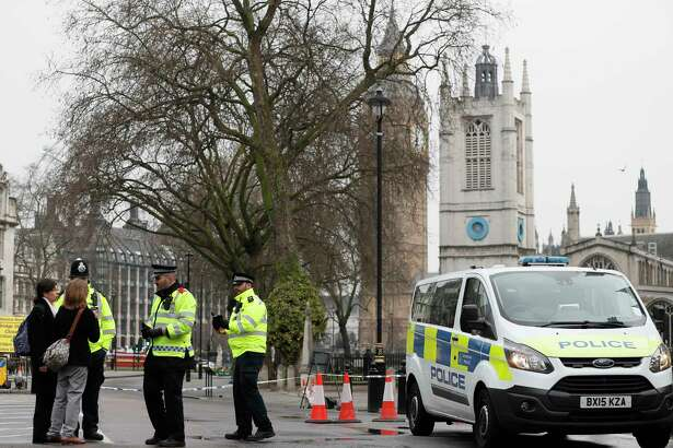 Police direct pedestrians around a cordon in place following Wednesday's terror attack, in London, Thursday March 23, 2017.  On Wednesday a knife-wielding man went on a deadly rampage, first  driving a car into pedestrians before stabbing a police officer to death and then was fatally shot by police within Parliament's grounds in London.  Five people were killed, including the assailant.