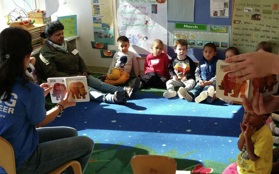 """KPMG volunteers read """"Brown Bear, Brown Bear, What Do You See?"""" to kids at the Children's Learning Centers of Fairfield County on Palmers Hill Road in Stamford, Conn., on Wednesday, March 22, 2017. The event was part of the firm's Family for Literacy program. Photo: Contributed / KPMG"""
