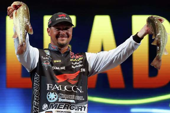 Jason Christie, from Park Hill, Okla., shows off two fish he caught on Day 2 of the Bassmaster Classic on March 5, 2016, in Tulsa, Okla.