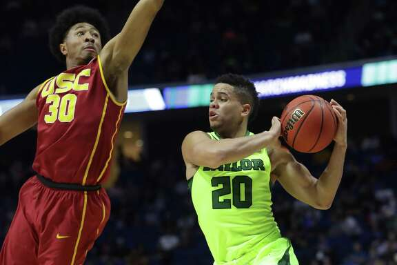 Manu Lecomte (20) of the Baylor Bears is defended by Elijah Stewart of the USC Trojans during the second round of the NCAA Tournament at BOK Center on March 19, 2017, in Tulsa, Okla.