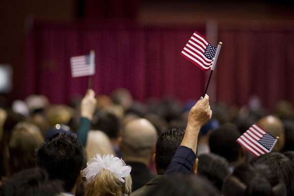 "People wave miniature American flags during a naturalization ceremony in San Diego, California, U.S., on Wednesday, March 22, 2017. Hawaii's attorney general is seeking to extend a temporary restraining order blocking Donald Trump's revised travel ban, citing the president's own words as evidence that the new policy is merely a ""subterfuge."" Photographer: David Maung/Bloomberg"
