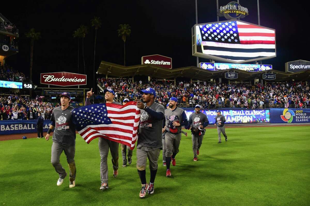 LOS ANGELES, CA - MARCH 22: Christian Yelich #7, Giancarlo Stanton #27 and Adam Jones #10 of team United States celebrate with the American Flag on the field after their 8-0 win over team Puerto Rico during Game 3 of the Championship Round of the 2017 World Baseball Classic at Dodger Stadium on March 22, 2017 in Los Angeles, California.