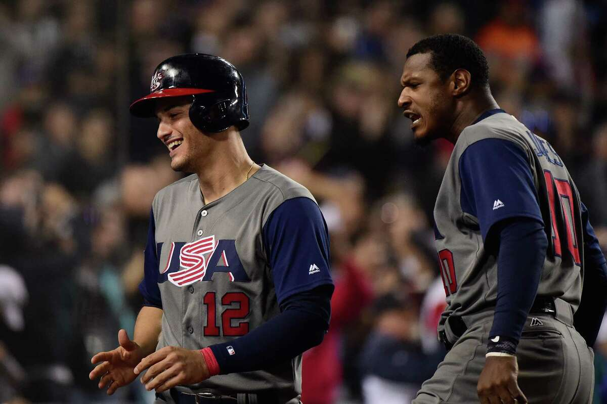 LOS ANGELES, CA - MARCH 22: Nolan Arenado #12 of team United States celebrates his run with Adam Jones #10 celebrates in the seventh inning against team Puerto Rico during Game 3 of the Championship Round of the 2017 World Baseball Classic at Dodger Stadium on March 22, 2017 in Los Angeles, California.