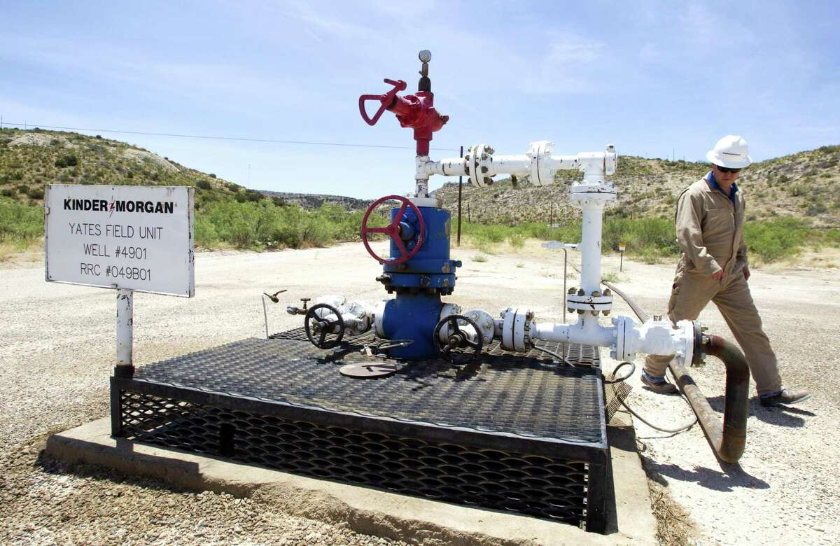 A Kinder Morgan operations manager walks past a well near Iraan's Yates oil field. The company is proposing to build a 42-inch, 430-mile natural gas pipeline from the Permian Basin to a point west of Corpus Christi for exports and domestic consumption.
