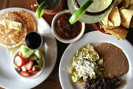 Food and drinks from the Saturday-Sunday brunch menu at Paloma Blanca restaurant in San Antonio.From left: Pancakes, a Strait Mule cocktail, a margarita, chips and a plate of Chilaquiles Distrito Federal with a rib-eye steak.