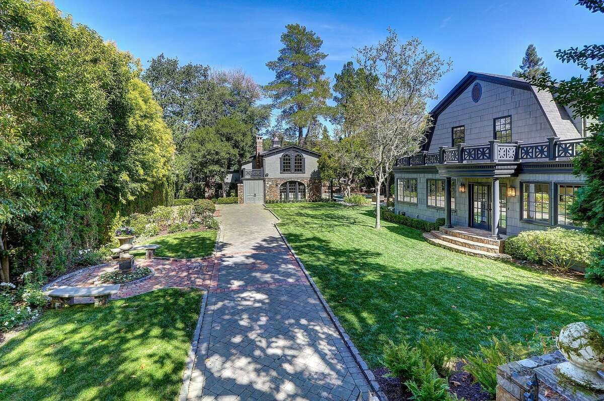 The gated landscape hosts verdant lawns that flank a custom paver driveway.�