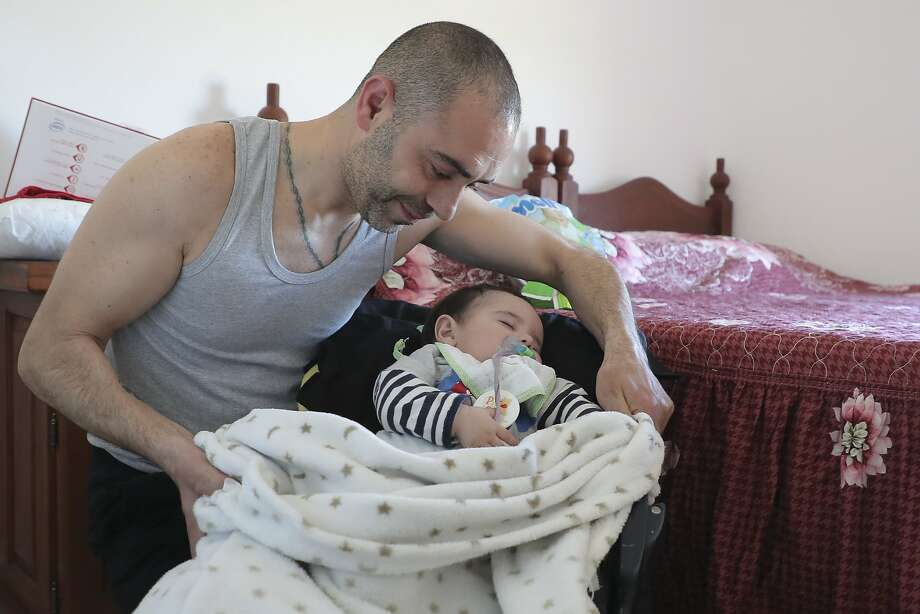 Syrian refugee Joseph K. places a blanket over his son, Aberlardo, in their new home in Argentina. Photo: Nicolas Aguilera, Associated Press