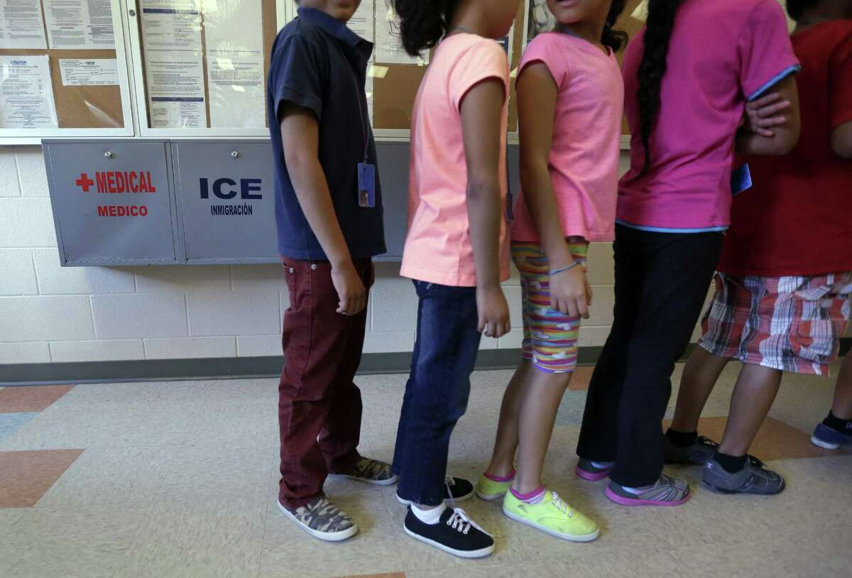 FILE - In this Sept. 10, 2014 file photo, detained immigrant children line up in the cafeteria at the Karnes County Residential Center, a temporary home for immigrant women and children detained at the border in Karnes City, Texas. The Justice Department says it will temporarily transfer immigration judges to six detention centers near the border with Mexico in an effort to put President Donald Trump's immigration directives into effect. (AP Photo/Eric Gay, File)