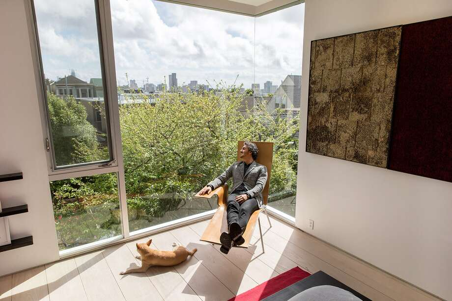 Amir Mortazavi lounges in the master bedroom, where floor-to-ceiling windows offer a view of S.F. Photo: Santiago Mejia, The Chronicle