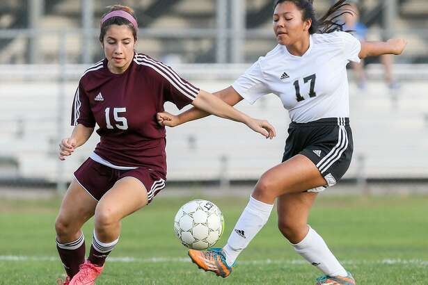 Highlands' Catalina Canizalez (left) fights for the ball with Edison's Ana Ruiz during a District 28-5A girls soccer game at the SAISD Sports Complex on Feb. 7, 2017.