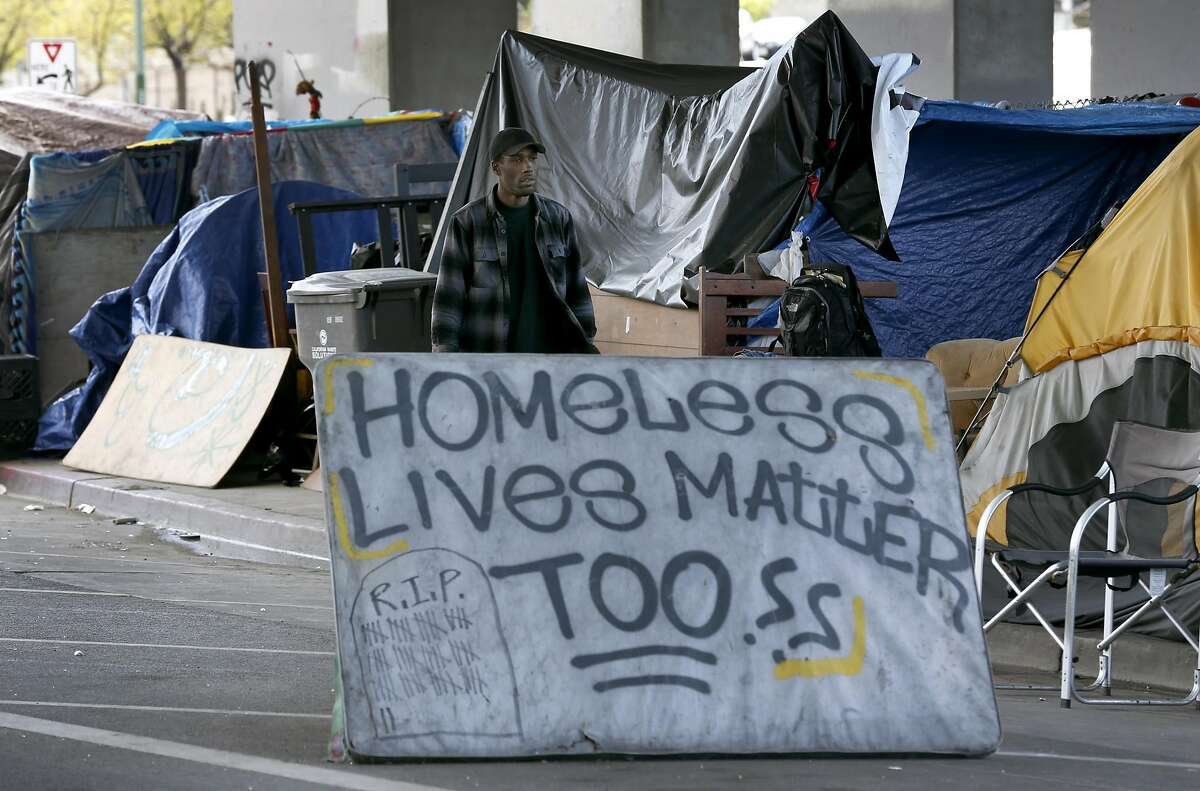 Shawn Moses walks behind the sign he created at a homeless encampment on Northgate Avenue below Interstate 980 in Oakland, Calif. on Thursday, March 23, 2017. Moses says he has lived in the camp for about three years, one of the longest established residents.