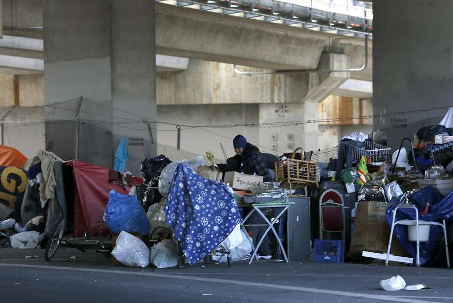 A homeless encampment on Northgate Avenue below Interstate 980 in Oakland is jam-packed with the campers' belongings and refuse. Photo: Paul Chinn, The Chronicle