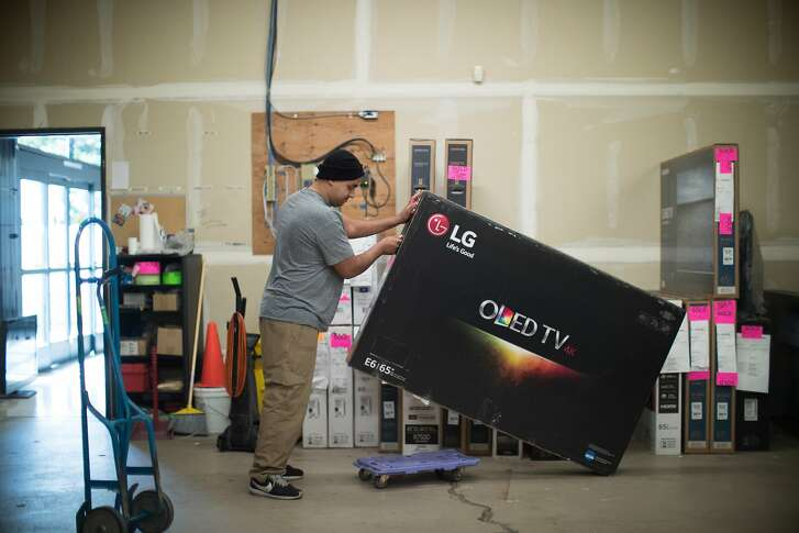 """Rigo Maldonado load a top of the line 65"""" 4K OLED TV for delivery from the stock room at Video Only in Dublin on Thursday, March 23, 2017 in Dublin, CA.   With a majority of new TV monitors sold in retail stores like Best Buy and Video Only are 4K UHD, but there are still no TV networks or stations that offer any 4K programming and almost no live broadcasts are available. Might be more coming later this year."""