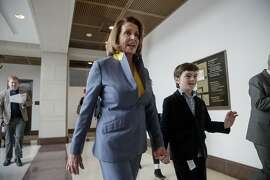 "House Minority Leader Nancy Pelosi of Calif., accompanied by her grandson Thomas, walks to a news conference on Capitol Hill in Washington, Thursday, March 23, 2017, as the GOP's long-promised legislation to repeal and replace ""Obamacare"" comes to a showdown vote. (AP Photo/J. Scott Applewhite)"