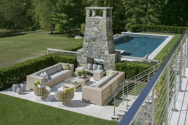 An outdoor fireplace employs stone called Old Redding Red, and the paving stones of Jerusalem gray limestone in a sandblasted finish.