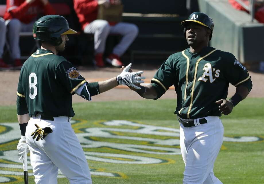 Oakland Athletics' Alejandro De Aza, right, celebrates with Jed Lowrie after scoring on a double by Mark Canha during the third inning of a spring baseball game in Mesa, Ariz., Sunday, Feb. 26, 2017. (AP Photo/Chris Carlson) Photo: Chris Carlson, Associated Press