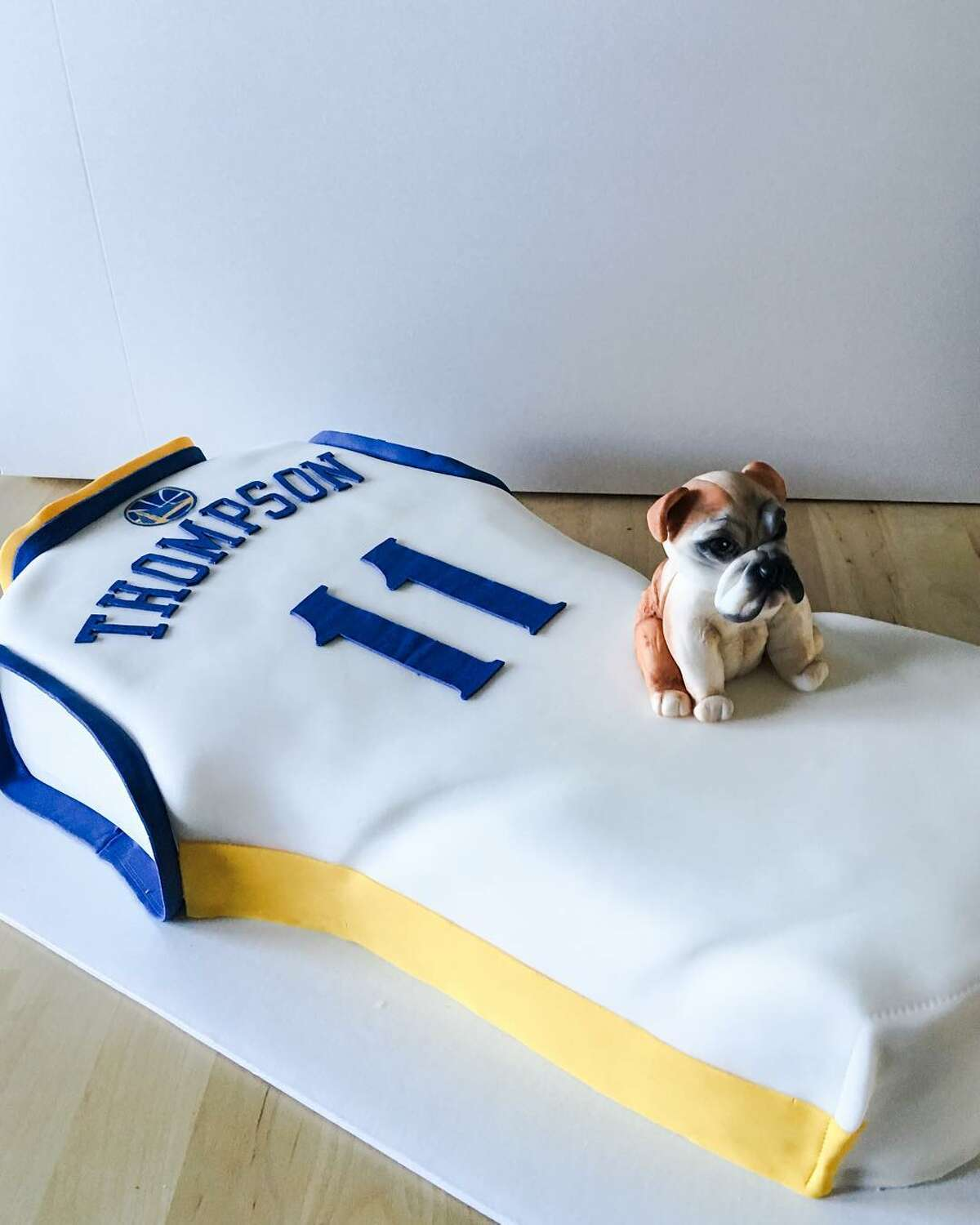 A birthday cake for Klay Thompson with a tiny Rocco made of sugar-gum paste.