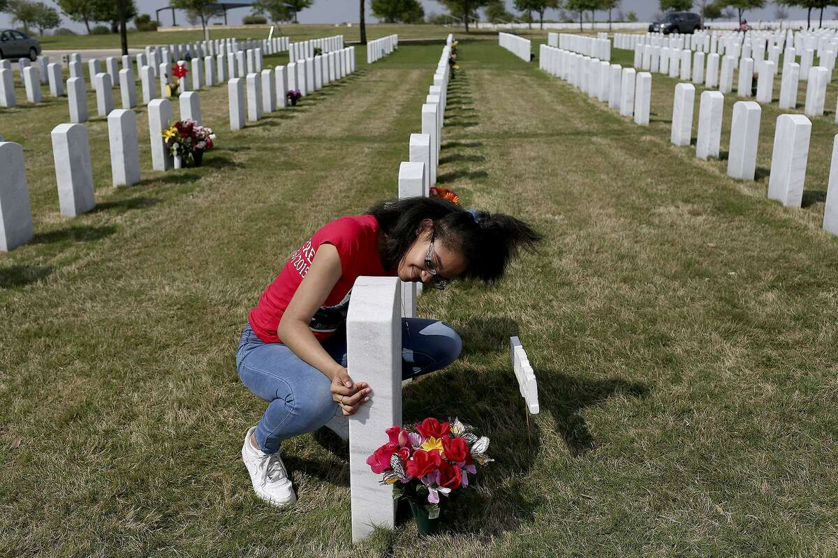 Dominique Trusty, 14, visits the grave of her brother, Tru Sincere Trusty, on what would have been his 18th brithday at Fort Sam Houston National Cemetery on Saturday, March, 18, 2017. Trusty was shot and killed when he was 16- years-old in September of 2015.