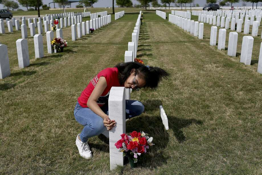 Dominique Trusty, 14, visits the grave of her brother, Tru Sincere Trusty, on what would have been his 18th brithday at Fort Sam Houston National Cemetery on Saturday, March, 18, 2017. Trusty was shot and killed when he was 16- years-old in September of 2015. Photo: Lisa Krantz / SAN ANTONIO EXPRESS-NEWS / SAN ANTONIO EXPRESS-NEWS