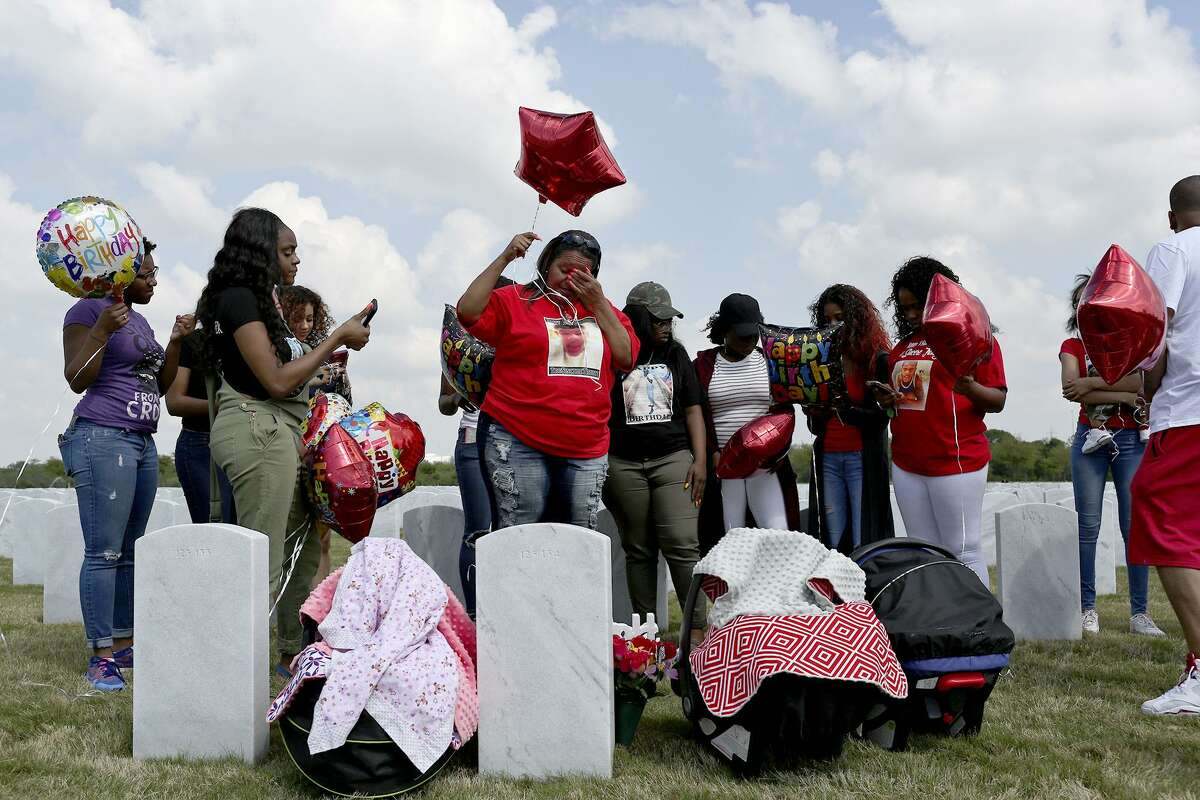 Olivia Fenner, center, gathers with friends and family for a balloon release for her son, Tru Sincere Trusty, on what would have been his 18th brithday at Fort Sam Houston National Cemetery on Saturday, March, 18, 2017. Trusty was shot and killed when he was 16- years-old in September of 2015.