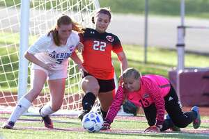 Oak Ridge goalie Kelsie Alexander (13) fights to make a stop against Round Rock forward Lauren Baker (22) as defender Grace Eason (5) assists during the first period of Region II-6A bi-district high school soccer playoff match at Palestine High School Thursday, March 22, 2017, in Palestine.