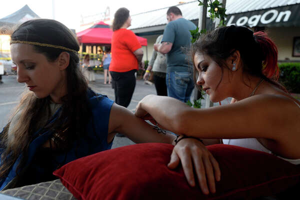 Amber Sumler gets a henna tattoo from Monica Arias during the Mini RenFest at The Logon Cafe on Thursday evening. Costumed revelers came to see performances by The Ukulady's Man and Belarusian band Stary Olsa.  Photo taken Thursday 3/23/17 Ryan Pelham/The Enterprise