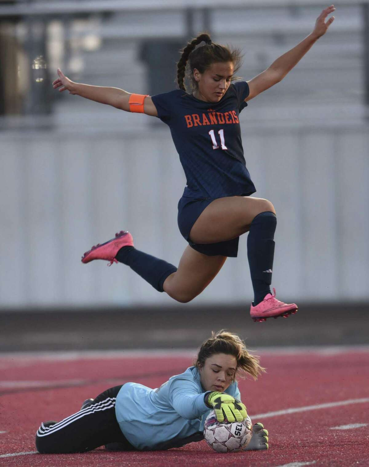 New Braunfels Canyon goalkeeper Alex Hayman makes a save as Samantha Palomino of Brandeis jumps during girls soccer action at New Braunfels Canyon High School on Thursday, March 23, 2017.