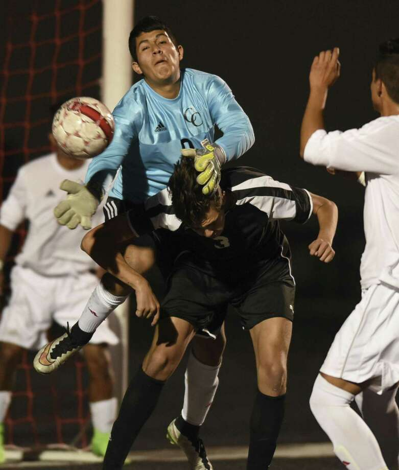 New Braunfels Canyon goalkeeper Omar Tinajero Gomez goes over Eduardo Ramirez of Clark on a corner kick during soccer action at New Braunfels Canyon High School on Thursday, March 23, 2017. Photo: Billy Calzada, Staff / San Antonio Express-News / San Antonio Express-News