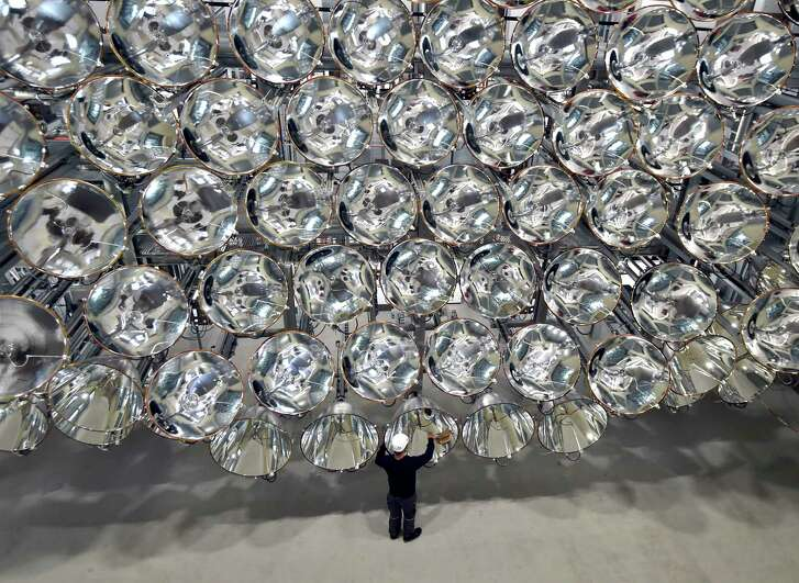 """An engineer stands in front of xenon short-arc lamps in Germany's DLR Institute for Solar Research. The lights are part of an """"artificial sun"""" that will be used for research purposes."""