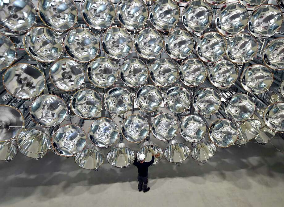 "An engineer stands in front of xenon short-arc lamps in Germany's DLR Institute for Solar Research. The lights are part of an ""artificial sun"" that will be used for research purposes.  Photo: Caroline Seidel, SUB / dpa"